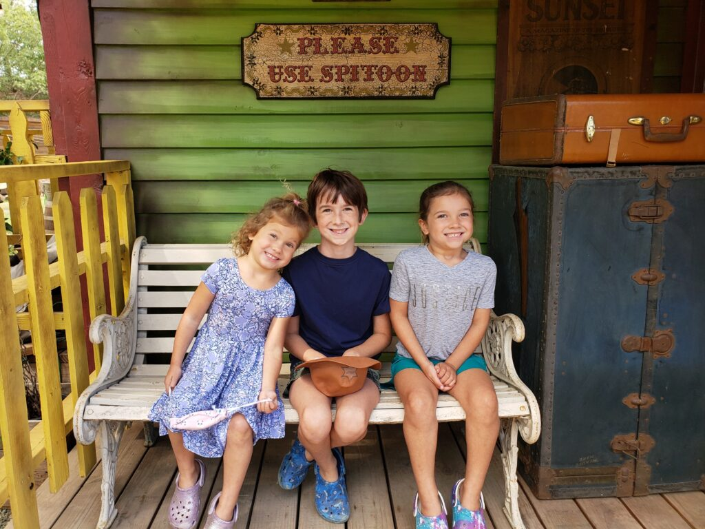 Three children smiling on bench at El Dorado Frontier