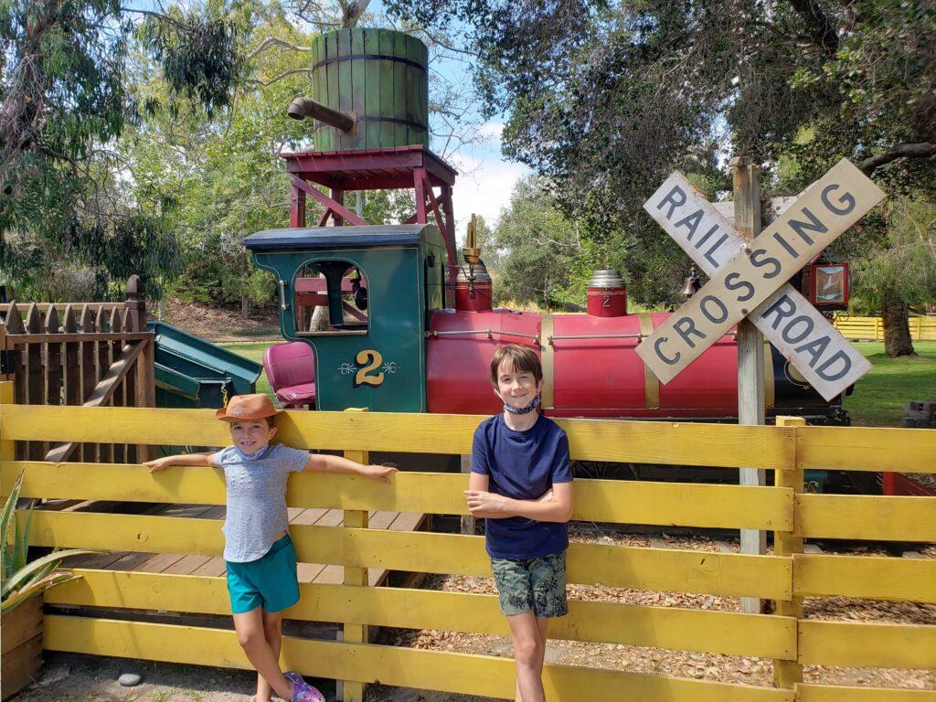 Two children in front of train ride at El Dorado Frontier