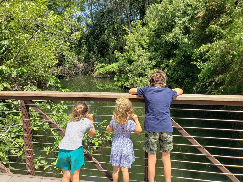 3 children on a bridge at the El Dorado Nature Center in Long Beach
