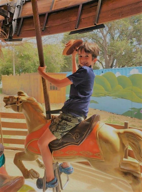Boy riding on carousel at El Dorado Frontier