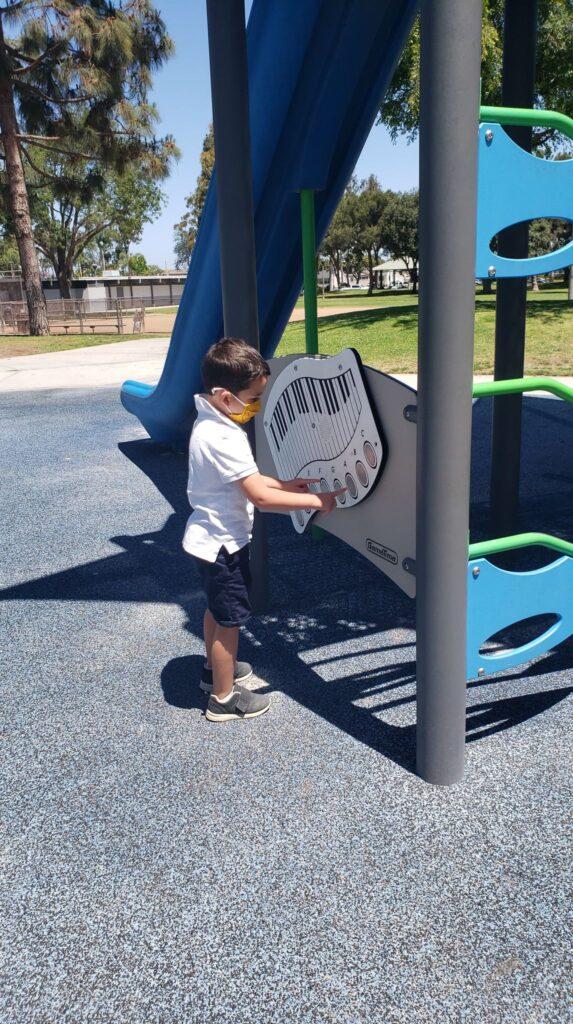 CHILD PLAYING MUSIC ON PLAYGROUND EQUIPMENT