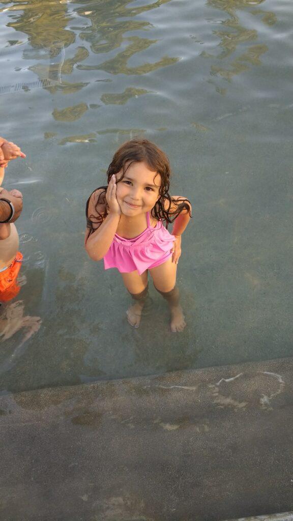 toddler swimming in wading pool