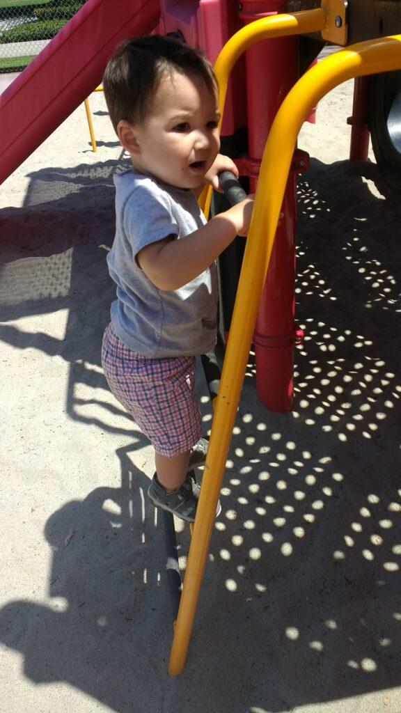 toddler climbing a play strucutre ladder