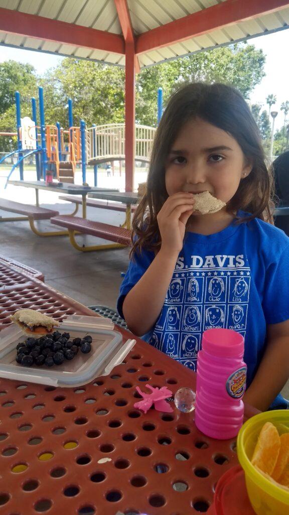 preschooler eating at a small picnic table